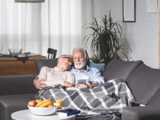 senior couple curled up under warm blankets for the eldelry
