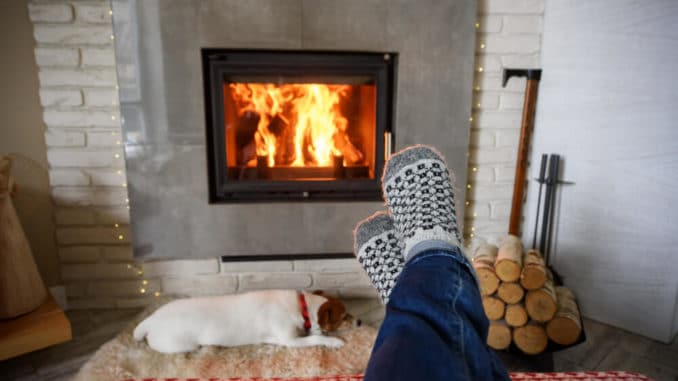 feet in warms socks for senior beside the fire