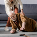 senior woman trying to lift elderly husband off of the floor