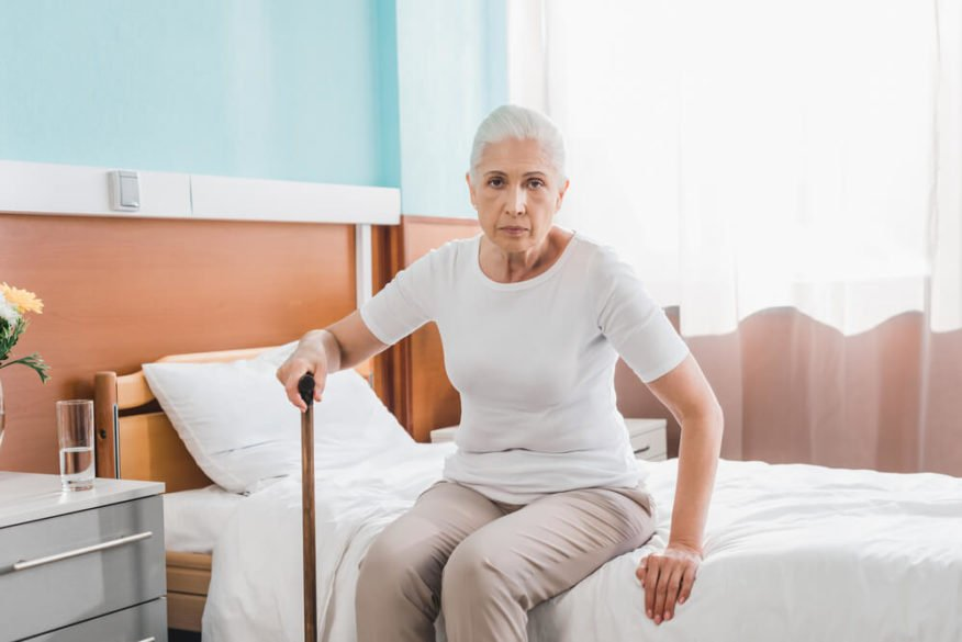 woman with dementia getting out of bed
