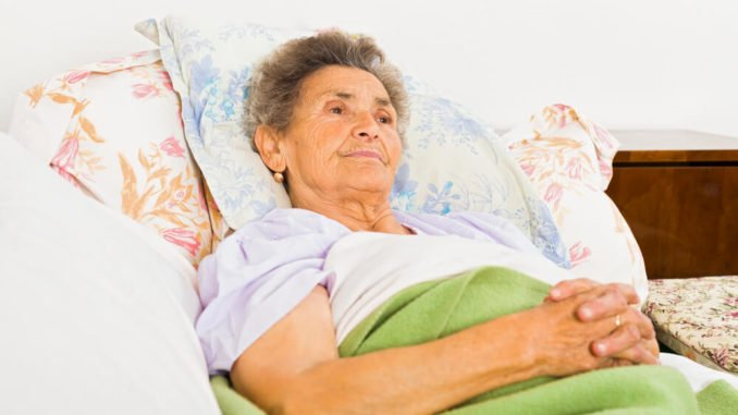 elderly woman propped up in bed under a weighted blanket