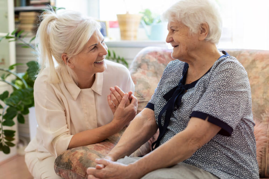 adult daughter discussing the past with her mother with dementia