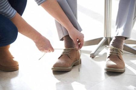 adult daughter tying her elderly parents shoe