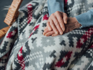 senior woman with hands folded on lap blanket for elderly