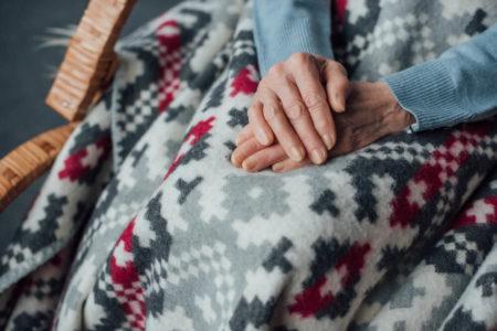senior woman with hands folded on lap blanket for elderly