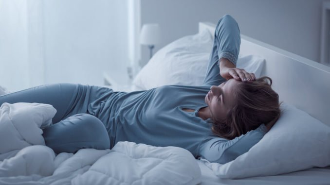 woman tossing and turning on her blankets from restless leg syndrome
