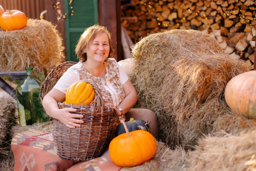 senior woman smiling with pumpkins at a fall festival.