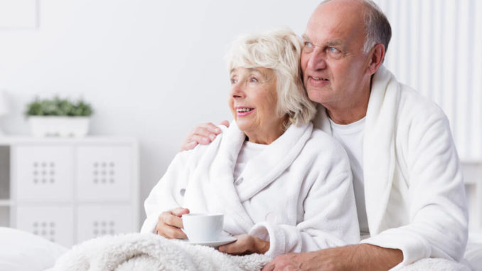 senior couple smiling while snuggled up under their heated weighted blanket