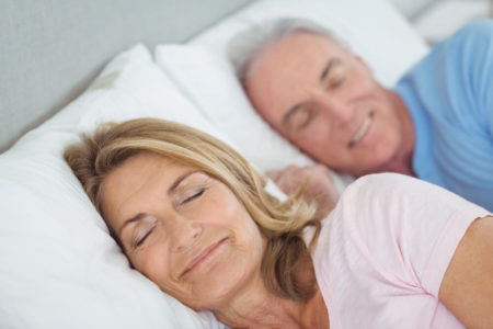 senior couple sleeping with weighted blanket that keeps you cool