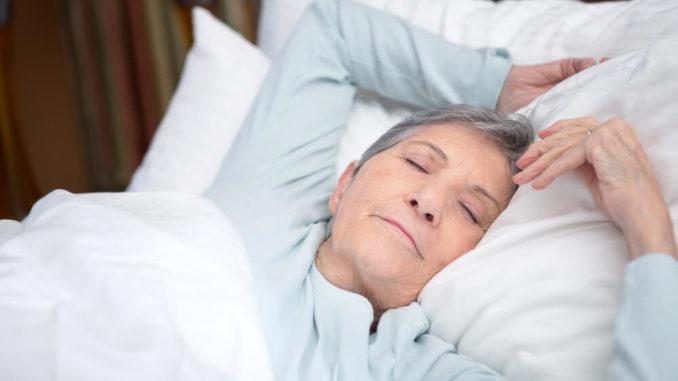 senior woman sleeping peacefully under her blankets