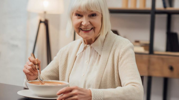 senior woman eating soup as a soft snack for the elderly