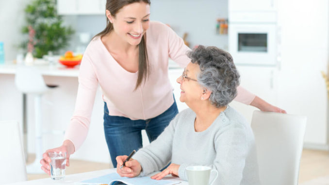 woman helping senior woman in the kitchen