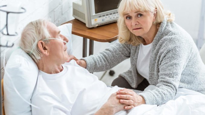 senior woman looking worried as her husband is lying in a hospital bed