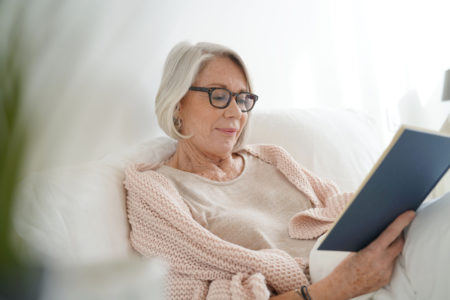 senior woman relaxing in bed reading covered with a weighted blanket