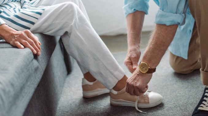 man tying shoes for elderly woman
