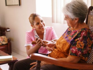 caregiver showing elderly woman how to use answering machine