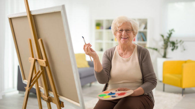 elderly woman painting a picture on an easel in her home.