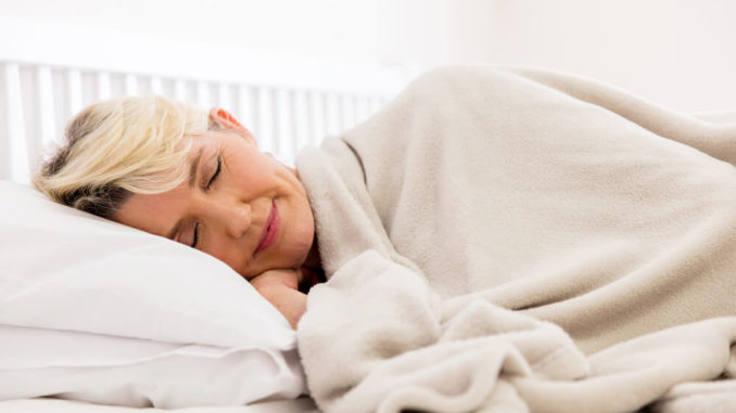 senior woman sleeping with weighted blanket for her anxiety