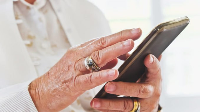 senior woman using a smartphone to call for help