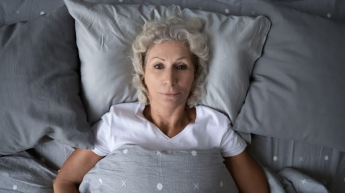 older woman laying in bed unable to sleep because of night terrors