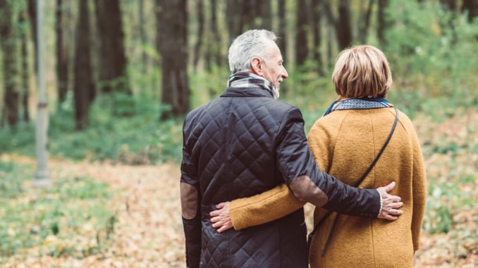 senior couple walking arm in arm in the autumn in a park