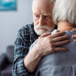 senior man hugging his wife with a sad look on his face