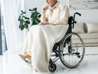 stroke patient sits in wheelchair with weighted blanket