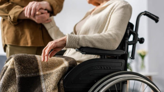 senior woman sitting in a wheelchair with a blanket on her lap