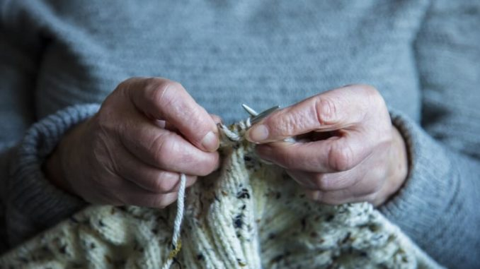 woman with dementia using her hands to knit