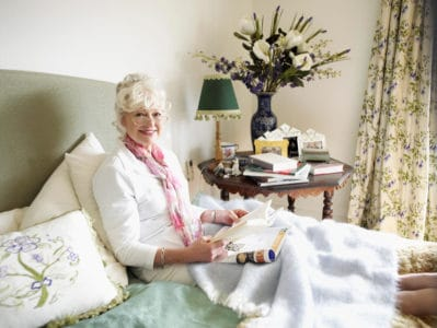bedridden senior woman playing games in bed