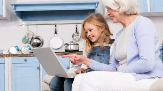 grandmother explaining online computer usage to her young granddaughter