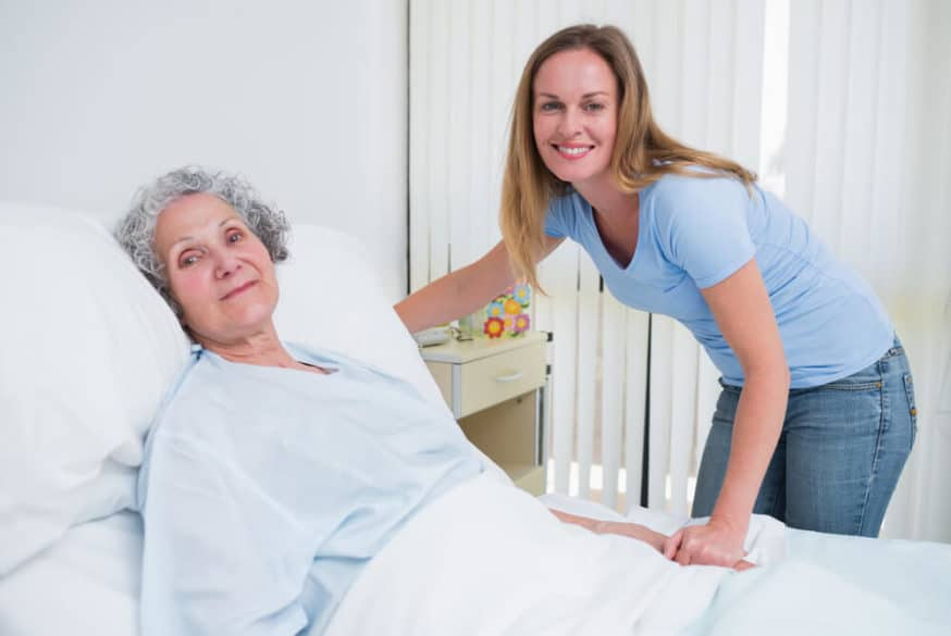 bedridden senior woman being visited by her granddaughter