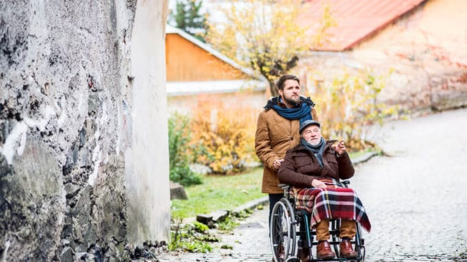 man pushing his father in a wheelchair with a blanket on his lap