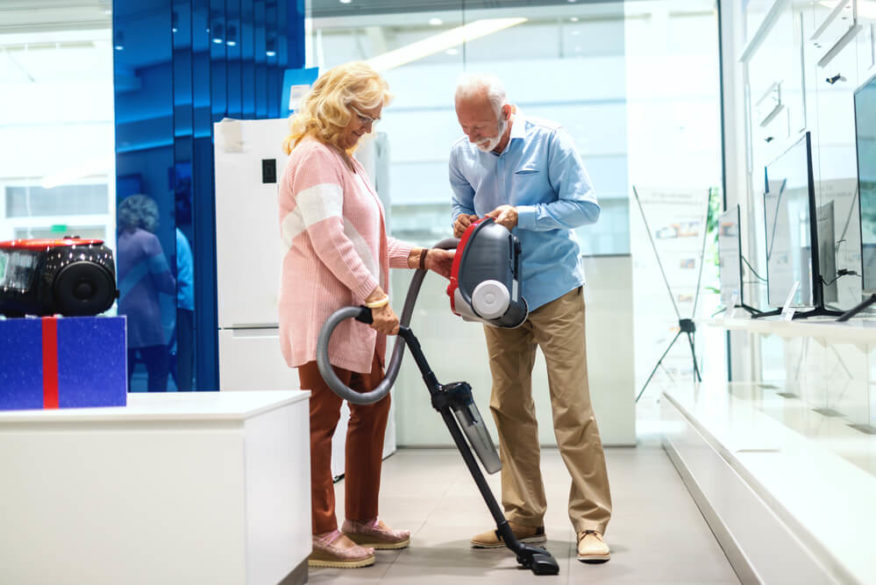 senior couple shopping for a new lightweight vacuum cleaner
