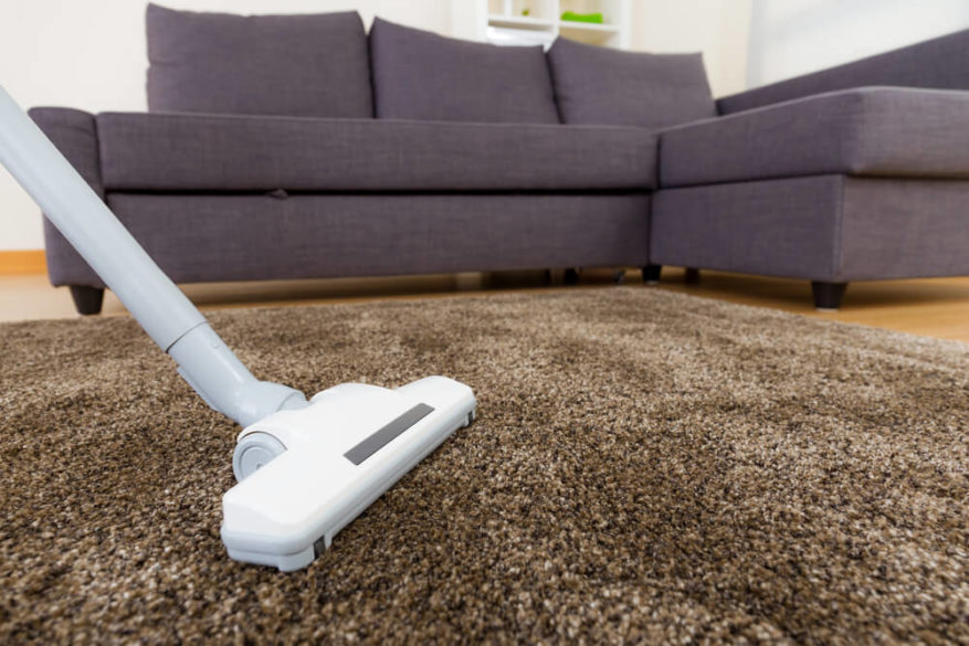 white vacuum cleaner on a carpet with hard floors in background