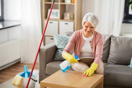 senior woman sitting while cleaning a table