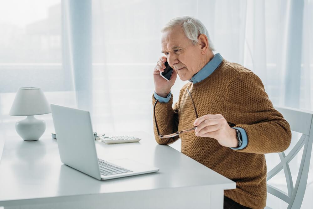 senior man using a telephone looking at his laptop