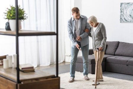 son walking his elderly mother with her cane on a safe rug