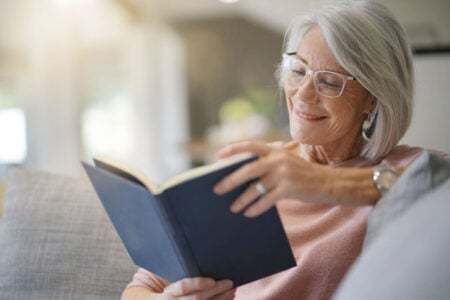 senior woman reading book with reading lamp