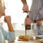 man with arthritic hands opening a wine bottle for his wife