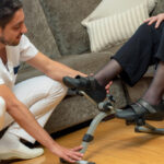 therapist showing senior lady how to use pedal exerciser