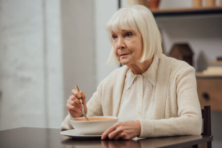 senior woman contemplating nutrition while eating soup