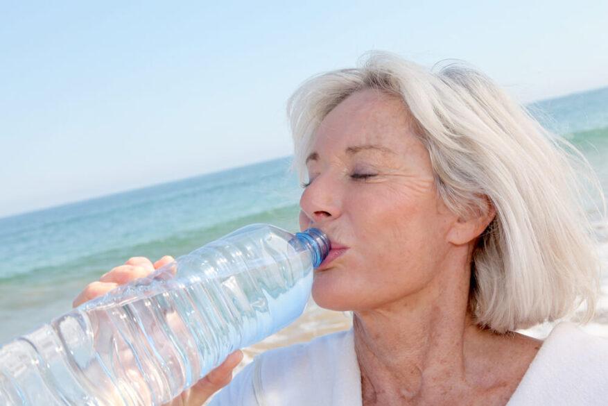 senior drinking water at beach