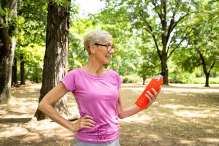 senior woman looking at energy drink in park
