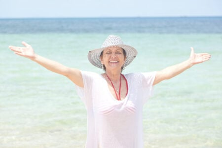 senior woman smiling on beach in a white cover up