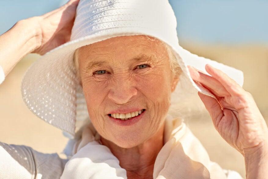 senior woman wearing a sun hat on the beach