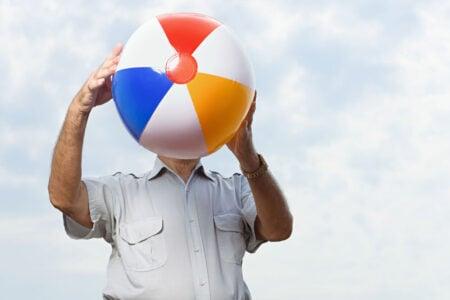 senior man exercising with beach ball